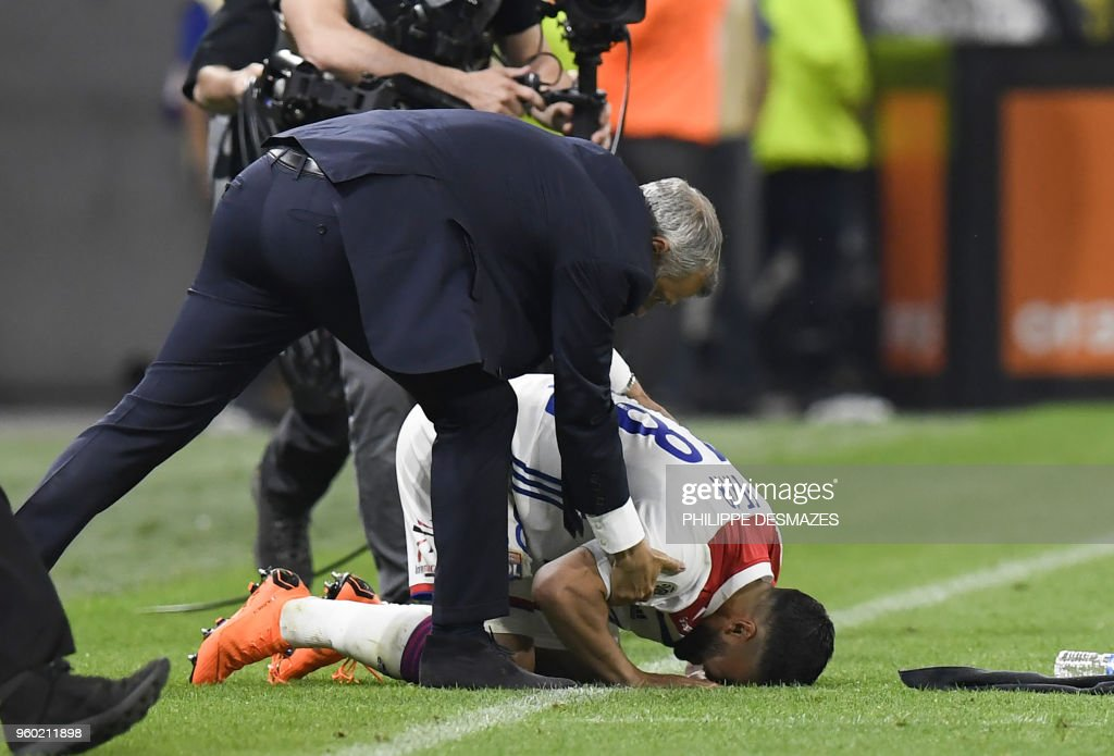Lyon's French midfielder Nabil Fekir (bottom), next to Lyon's French head coach Bruno Genesio (up), reacts after winning the French L1 football match between Olympique Lyonnais and OGC Nice, on May 19, 2018, at the Groupama Stadium in Decines-Charpieu near Lyon, central-eastern France.