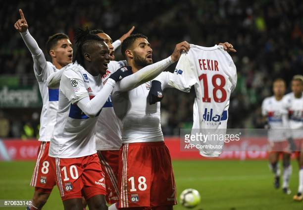 TOPSHOT Lyon's French midfielder Nabil Fekir shows his shirt as is congratulated by team mates after scoring during the French L1 football match...