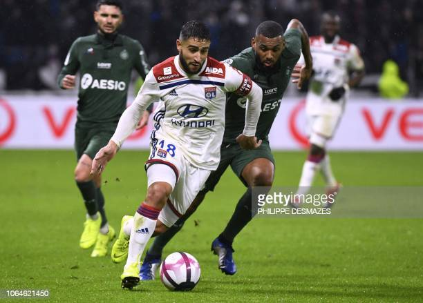 Lyon's French midfielder Nabil Fekir vies with Saint-Etienne's French midfielder Yann M'vila during the French L1 football match between Lyon and...