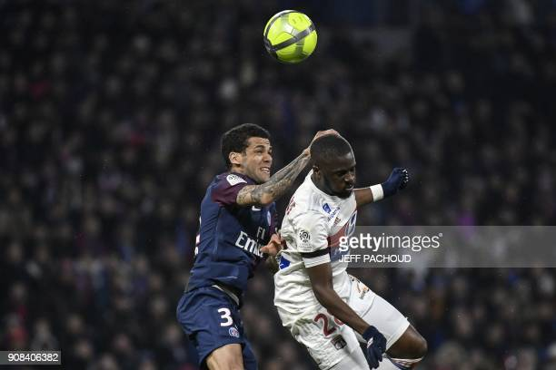 Lyon's French midfielder Tanguy Ndombele heads the ball with with Paris Saint-Germain's Brazilian defender Daniel Alves during the French L1 football...