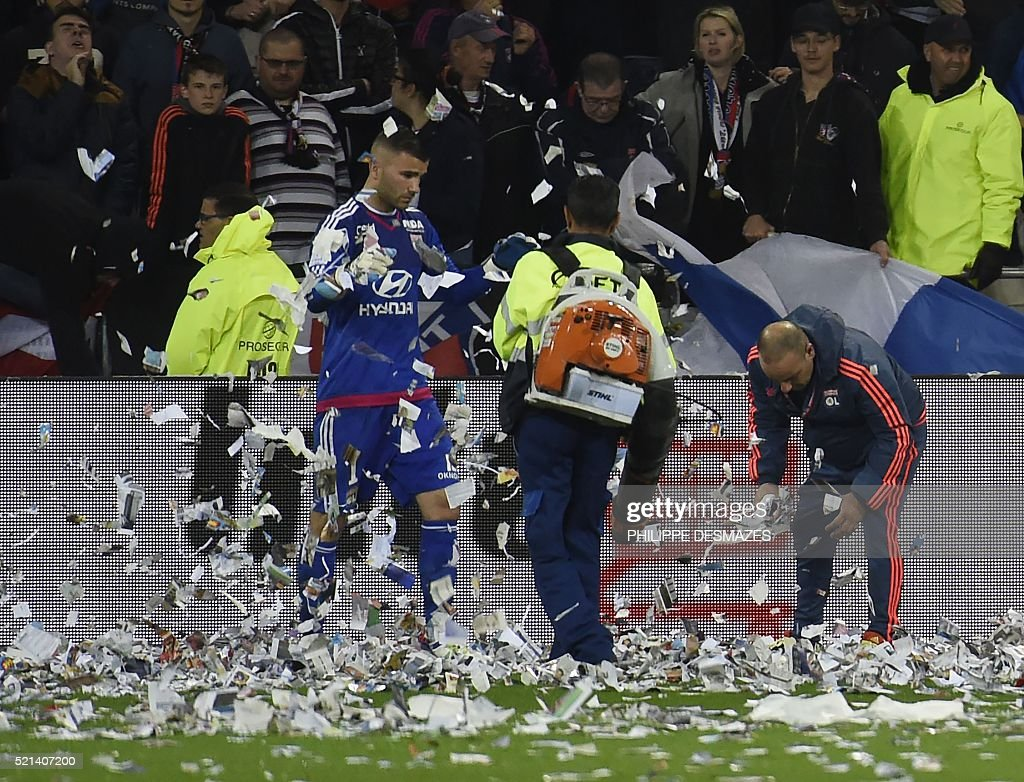Lyon's French-Portuguese defender Anthony Lopes (L) helps workers to clean the papers thrown on the field by fans during the French L1 football match Olympique Lyonnais and OGC Nice on April 15, 2016, at the New Stadium in Decines-Charpieu near Lyon, southeastern France.
