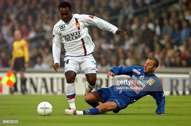 Lyon's Ghanean midfielder Mickael Essien is tackled by Bastia's forward Florian Maurice during their French first league football match 12 May 2004...