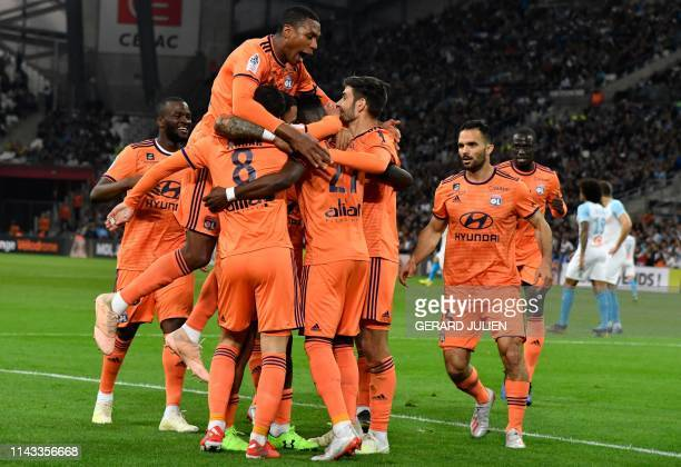 Lyon's Ivorian forward Maxwell Gnaly Cornet is congratulated by Lyon's players after scoring a goal during the French L1 football match between...