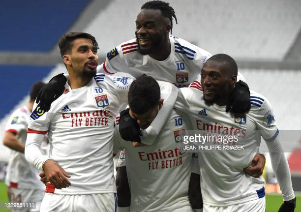 Lyon's Ivorian forward Maxwell Cornet celebrates with Lyon's Cameroonian forward Karl Toko Ekambi and Lyon's Brazilian midfielder Lucas Paqueta...