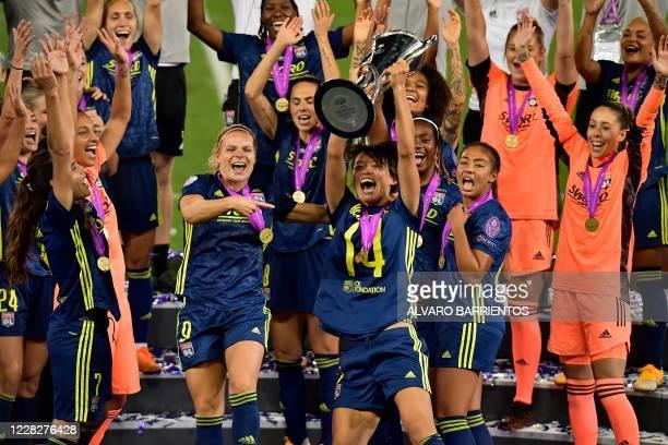Lyon's Japanese midfielder Saki Kumagai raises the trophy as she celebrates with teammates after winning the UEFA Women's Champions League final...