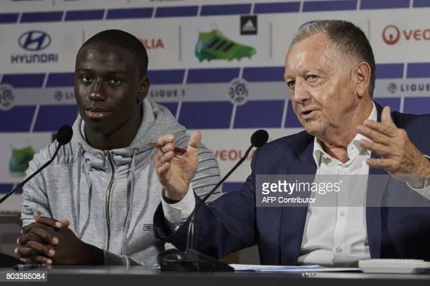 Lyon's L1 football club French new defender Ferland Mendy listens to Lyon's French president Jean-Michel Aulas during a press conference on June 29,...