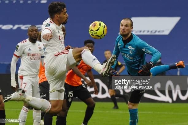 Lyon's midfielder Lucas Coelho De Lima jumps to control the ball in front of Reims' Serbian goalkeeper Predrag Rajkovic during the French L1 football...