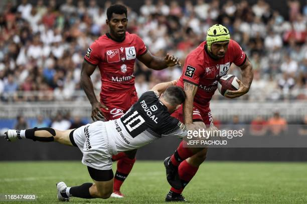 Lyon's New Zealander center Charlie Ngatai is tackled by Toulouse's Australian flyhalf Zack Holmes during the French Top 14 rugby union match between...