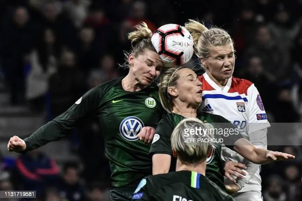 TOPSHOT Lyon's Norwegian forward Ada Hegerberg heads the ball with Wolfsburg's German midfielder Lena Goessling and Wolfsburg's German forward...