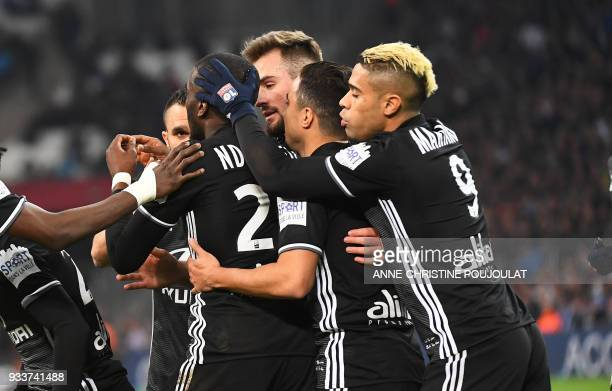 Lyon's players celebrate after Olympique de Marseille's French defender Adil Rami scored an own goal during the French L1 football match Marseille vs...