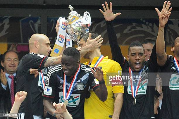 Lyon's players celebrate holding the trophy after winning the French Cup final football match Olympique Lyonnais vs US Quevilly on April 28 2012 at...