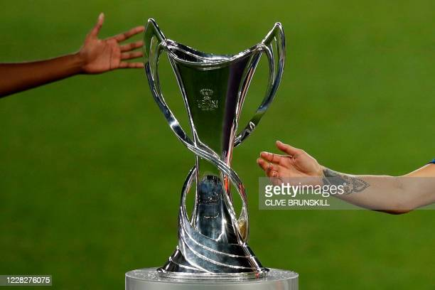 Lyon's players tend towards the trophy after Lyon won the UEFA Women's Champions League final football match between VfL Wolfsburg and Lyon at the...