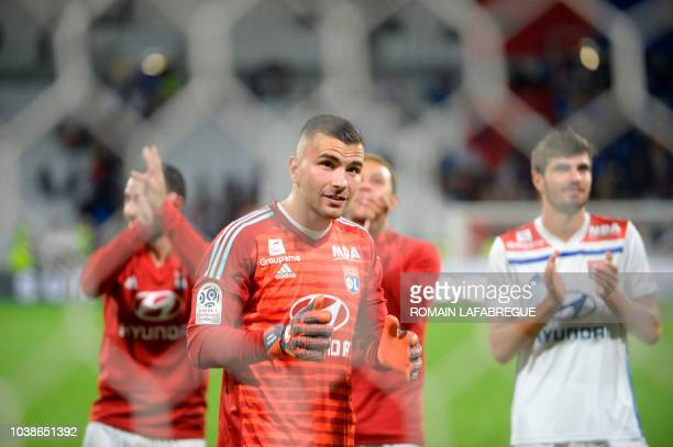 Lyon's Portuguese goalkeeper Anthony Lopes and team mates celebrate with supporters after winning the French L1 football match between Lyon and...