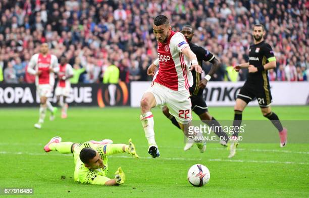 Lyon's Portuguese goalkeeper Anthony Lopes vies with Ajax midfielder Hakim Ziyech during UEFA Europa League semifinal first leg Ajax Amsterdam v...