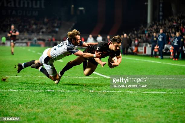 Lyon's scrumhalf Baptiste Couilloud scores a try despite Agen's scrumhalf Paul Abadie during the French Top 14 rugby union match between Lyon and...