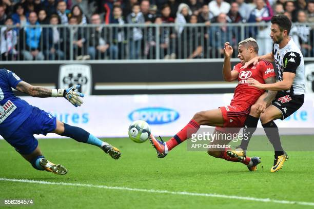 Lyon's Spanish forward Mariano Diaz vies with Angers' French defender Romain Thomas and scores against Angers' French goalkeeper Alexandre Letellier...