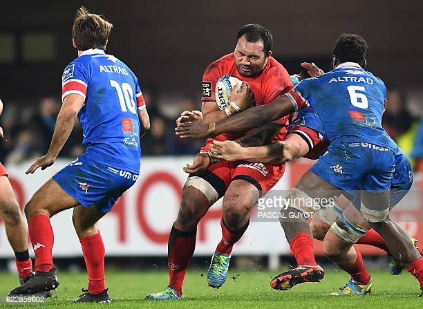 Lyon's Tongan flanker Taïasina Tuifua vies with Montpellier's South African flyhalf Demetri Catrakilis and Montpellier's French flanker Fulgence...