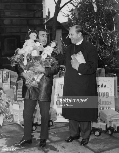Lyricist and composer Lionel Bart with an armful of toys next to Reverend Gordon Taylor the vicar of St GilesintheFields on the corner of Denmark...