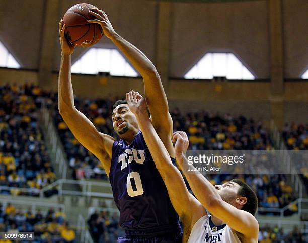 Lyrik Shreiner of the TCU Horned Frogs pulls down a rebound against Nathan Adrian of the West Virginia Mountaineers during the game at the WVU...