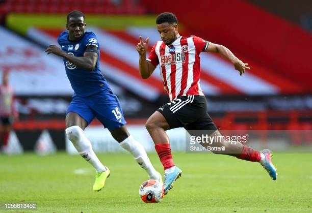 Lys Mousset of Sheffield United breaks through with the ball whilst under pressure from Kurt Zouma of Chelsea during the Premier League match between...