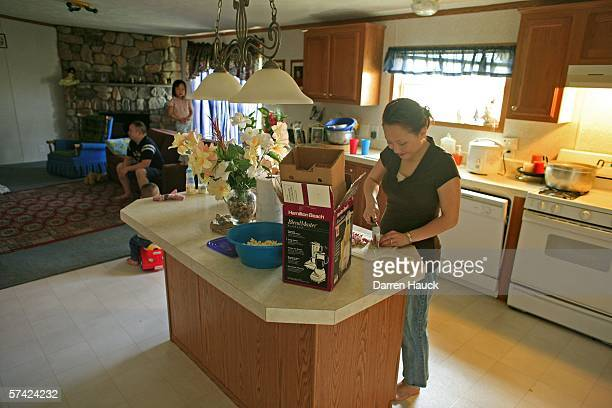 Lysauke Yang a Hmong immigrant watches television with three of his five children as wife Joyce prepares food after Lysauke returned from the morning...