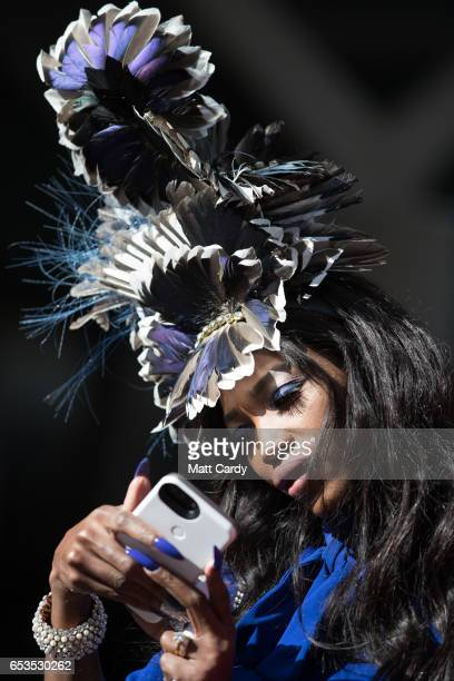 Lystra Adams looks at her phone as she arrives at the Cheltenham Racecourse on Ladies Day the second day of the Cheltenham Festival on March 15 2017...