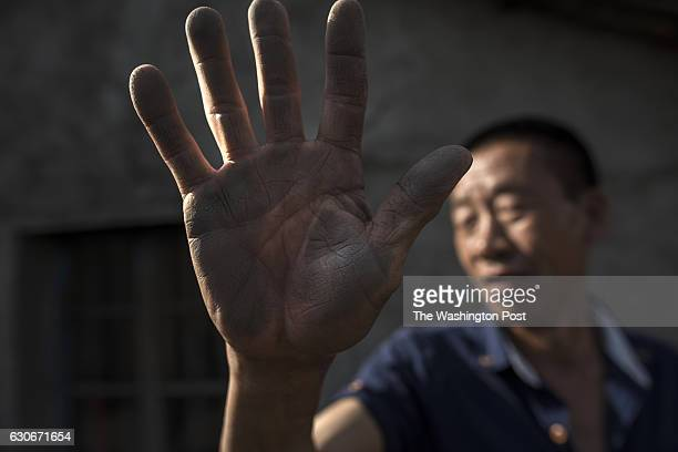 MASHAN CHINA MAY 28 Lyu Shengwen shows the graphite dust he collected on the side of his house which he cleaned the day before in the town of Mashan...