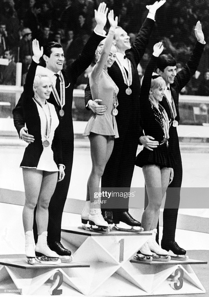 Lyudmila Belousova and her partner Oleg Protopopov (C), flanked by West Germans Marika Kilius and Hans-Jnrgen BSumler (L) and Canadians Debbi Wilkes and Guy Reveil, wave to the crowd on the podium of the figure skating pairs competition 15 february 1968 in Innsbruck. The Soviet couple won the Olympic gold medal in front of the Germans and the Canadians.
