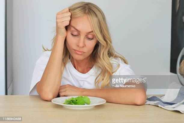 i'm fed up with untasty disgusting salad. close up unhappy grimacing sad upset lady looking down at plate of lettuce on table. - hungry stock pictures, royalty-free photos & images