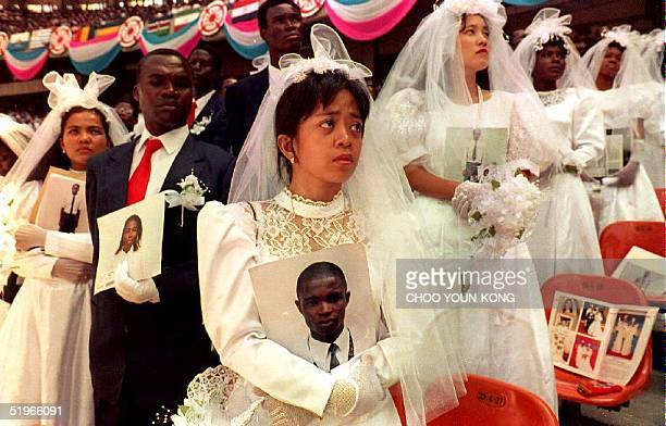 Ma Espirita of the Philippines holds a picture of her spouse Nwosu Unhei of Nigeria who was unable to attend the Unification Church wedding ceremony...