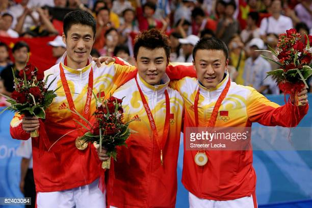 Ma Lin Wang Hao and Wang Liqin of China celebrate their gold medal in the Men's Team Contest at the Peking University Gymnasium on Day 10 of the...