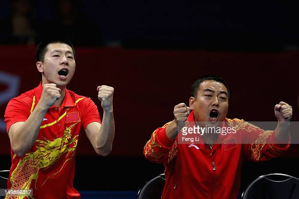 Ma Long and coach Liu Guoliang of China celebrates during Men's Team Table Tennis quarterfinal match against team of Singapore on Day 9 of the London...