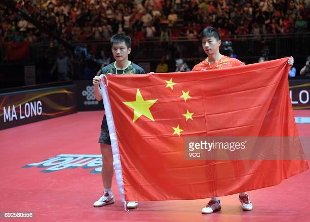 Ma Long and Fan Zhendong of China hold a national flag after their Men's Singles Final during Table Tennis World Championship at Messe Duesseldorf on...