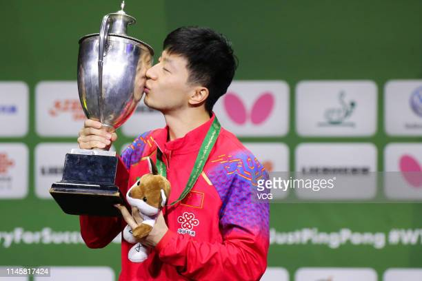 Ma Long of China kisses the trophy on the podium after winning the Men's Singles final match against Mattias Falck of Sweden on day eight of the ITTF...