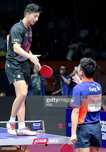 Ma Long of China shakes hands with Fang Bo of China after winning men's singles final match on day eight of the 2015 World Table Tennis Championships...