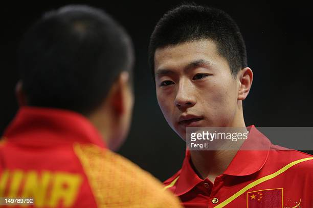 Ma Long of China speaks with his coach Liu Guoliang during Men's Team Table Tennis first round match against team of Russia on Day 8 of the London...