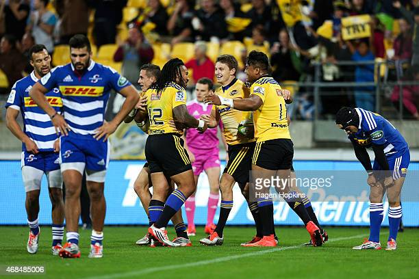 Ma'a Nonu Beauden Barrett and Julian Savea of the Hurricanes celebrate Barrett's try during the round eight Super Rugby match between the Hurricanes...