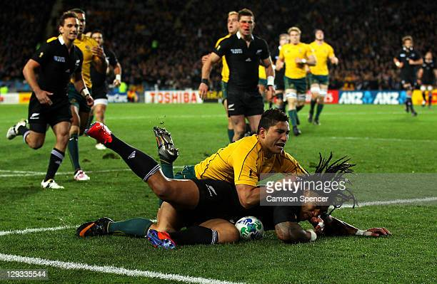 Ma'a Nonu of the All Blacks slides over to score the opening try of the match despite the tackle from Anthony Fainga'a of the Wallabies during semi...