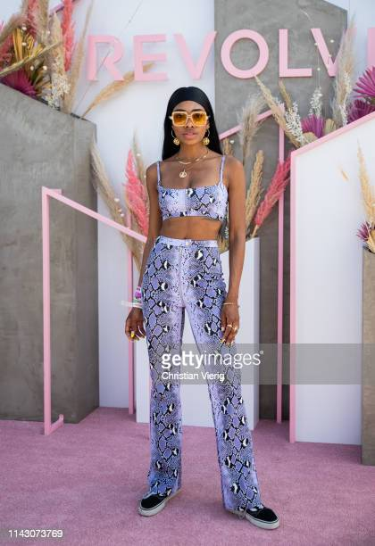 Maad is seen wearing head scarf sunglasses earrings cropped top with snake print and pants at Revolve Festival during Coachella Festival on April 14...