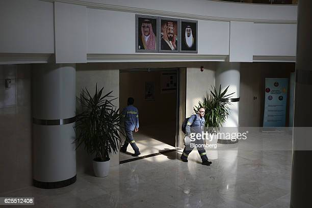 Ma'aden workers walk through the hallway and underneath portraits of the Saudi Royal family displayed inside the offices of the aluminium facility at...