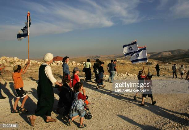 Israeli settlers march 23 May 2006 holding up Israeli flags to the outpost of Maale Rehavam in the West Bank to protest against the wish of Israeli...
