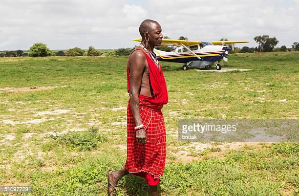 Maasai and safari palne on African savannah