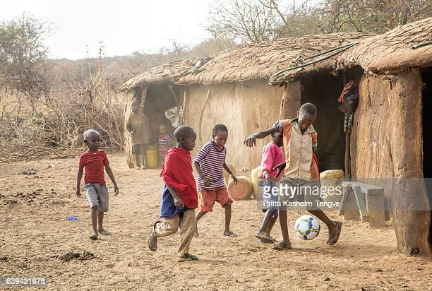 maasai boys playing football (soccer) in kenya village, africa - shack stock pictures, royalty-free photos & images