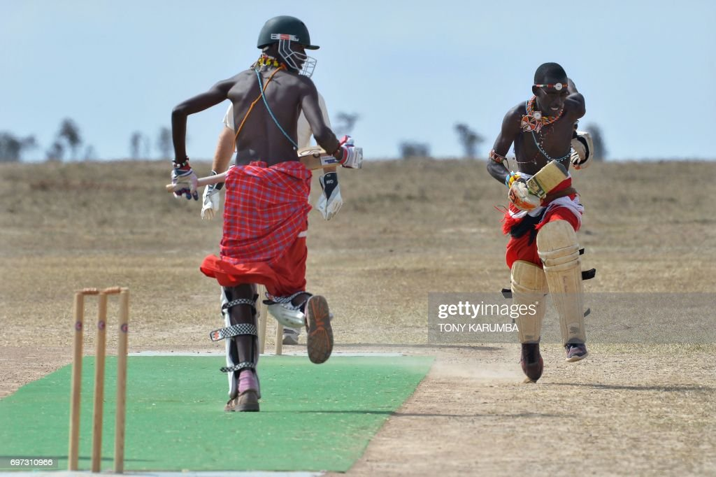 Maasai cricket warriors score a run against opponents from the British Army Training Unit Kenya (BATUK) team on June 18, 2017 during a cricket tournament played in the wilds of Laikipia county's Ol-Pejeta Conservancy, at the foot of Mount Kenya, and home to the last three northern white rhino sub-species on the planet. The two-day tournament dubbed 'Last Male Standing' is an annual charity event that aims to raise awareness of the plight of the nothern-white rhino and creates funding to continue ongoing research into ways to save the sub-species from extinction. /