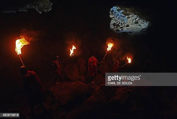 Maasai elder Jeremiah Saitabao walks with students holding flaming torches during a tutorial for younger Maasai men at Suswa caves on May 22 2014...