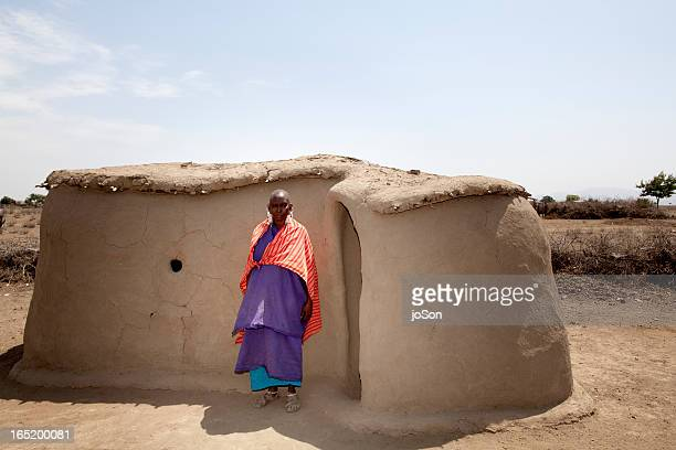 Maasai elder stand in front of her home