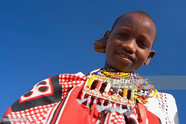 Maasai girl (9-11) outdoors, smiling, portrait, low angle view