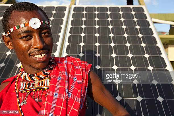 Maasai man standing in front of solar panels
