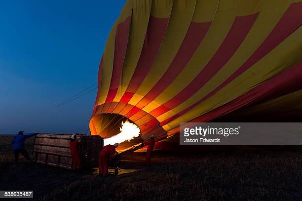 A gas jet flame fills a hot air balloon at dawn for a tourist flight over the African savannah.