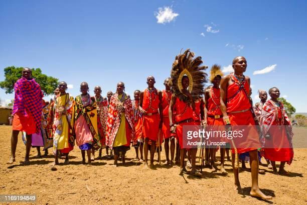 hommes et femmes maasai utilisant des vêtements traditionnels - masai photos et images de collection
